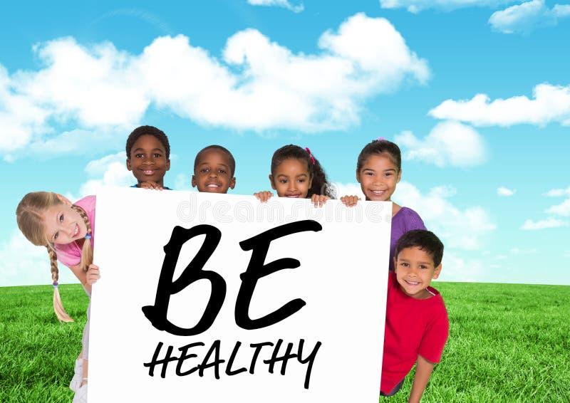 As crianças que guardam o cartão que mostra o texto sejam saudáveis na frente do céu azul e da grama imagens de stock royalty free