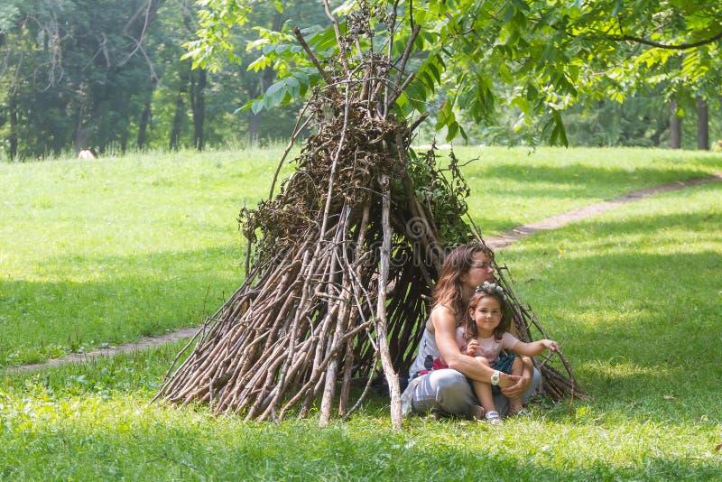 As crianças que jogam ao lado da vara de madeira abrigam a vista como a cabana indiana, foto de stock royalty free