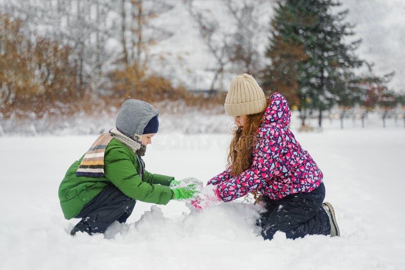 As crianças que jogam com um boneco de neve em um inverno andam no parque imagens de stock
