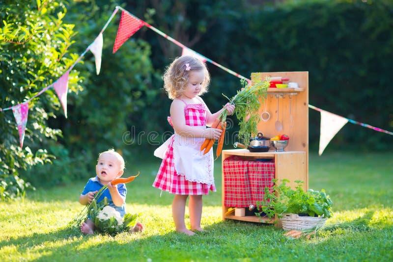 As crianças que jogam com uma cozinha do brinquedo em um verão jardinam imagens de stock