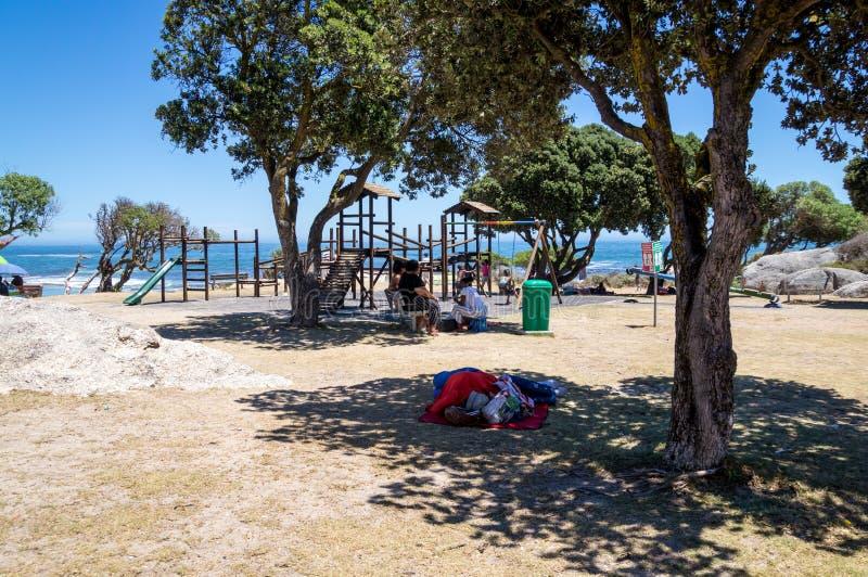 As crianças que jogam no campo de jogos dos acampamentos latem praia imagens de stock