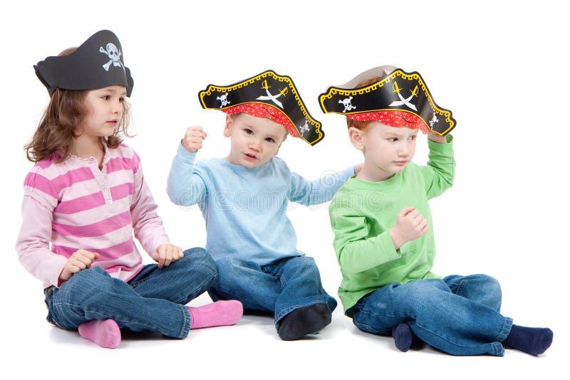 As crianças que jogam o jogo nos miúdos party chapéus do pirata fotografia de stock royalty free