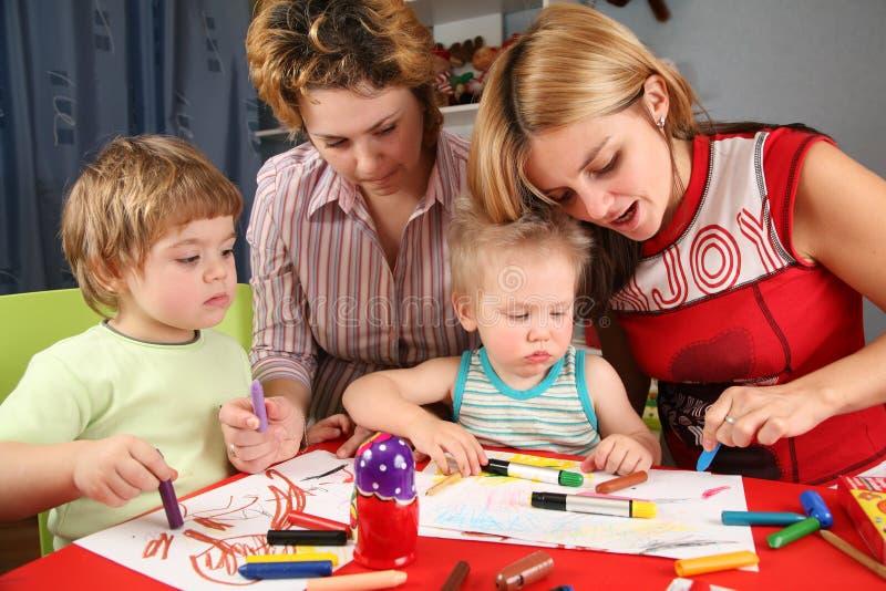 As crianças que pintam com sua serem de mãe a 2 foto de stock