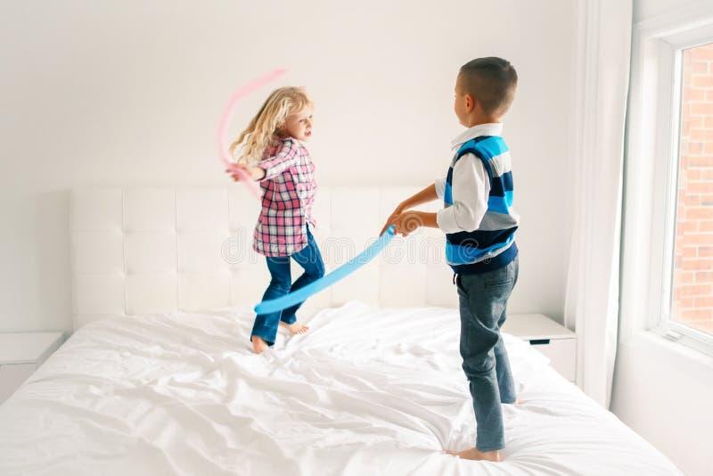 As crianças que saltam na cama no quarto e no jogo foto de stock royalty free