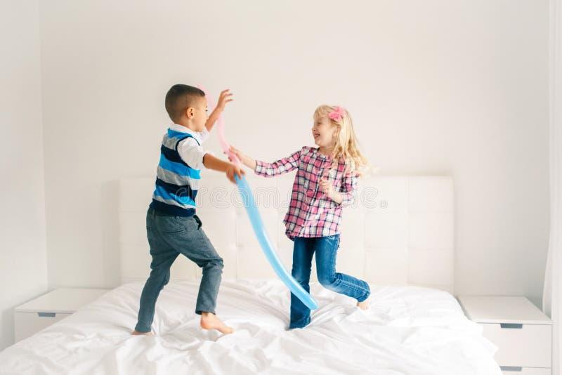 As crianças que saltam na cama no quarto e no jogo fotografia de stock