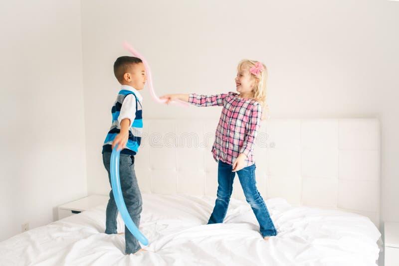 As crianças que saltam na cama no quarto e no jogo imagem de stock