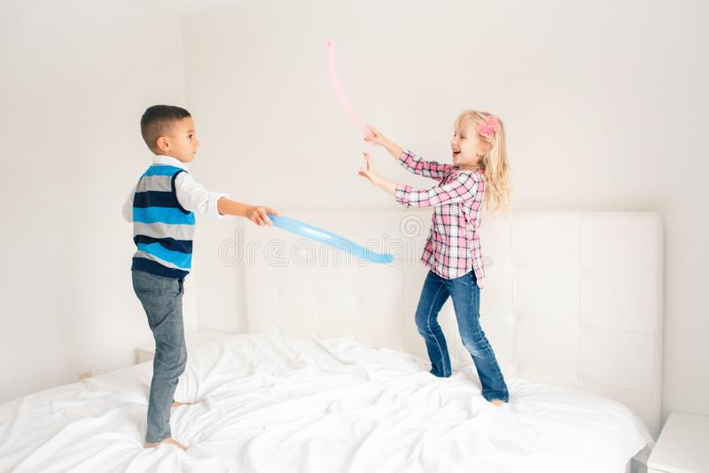 As crianças que saltam na cama no quarto e no jogo imagens de stock