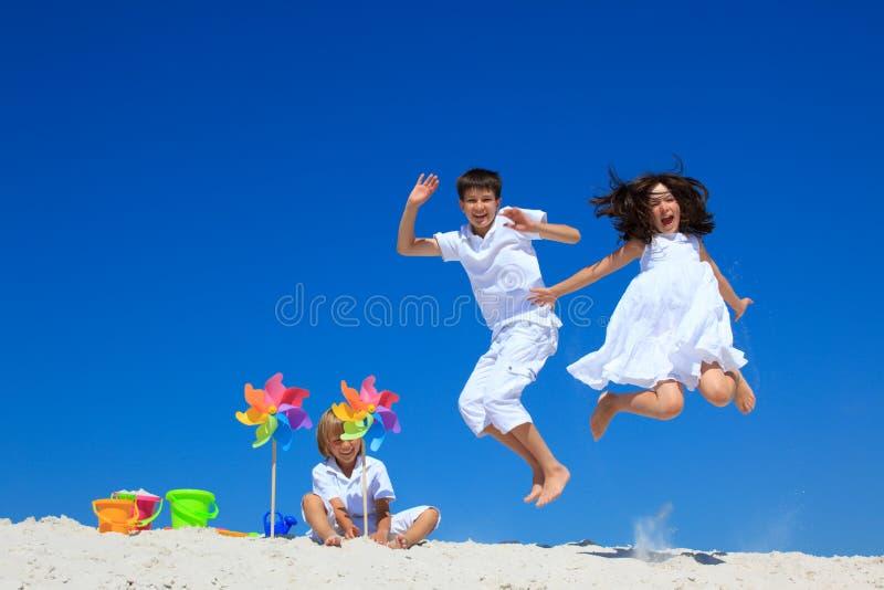 As crianças que saltam na praia fotos de stock royalty free