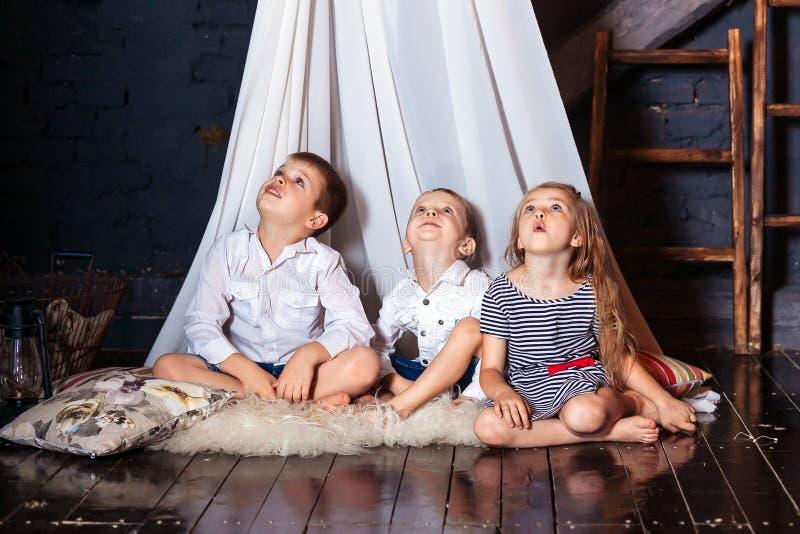 As crianças que sentam junto irmãs dos irmãos das meninas dos meninos os olhos azuis do olhar que em seguida sentam o assoalho br fotos de stock