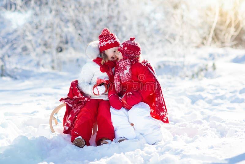 As crianças que sledding em crianças da floresta do inverno bebem o cacau quente na neve imagens de stock royalty free