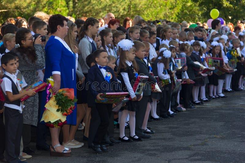 As crianças registraram-se na primeira classe com os presentes nas mãos dos professores e dos estudantes da High School na linha  fotografia de stock royalty free
