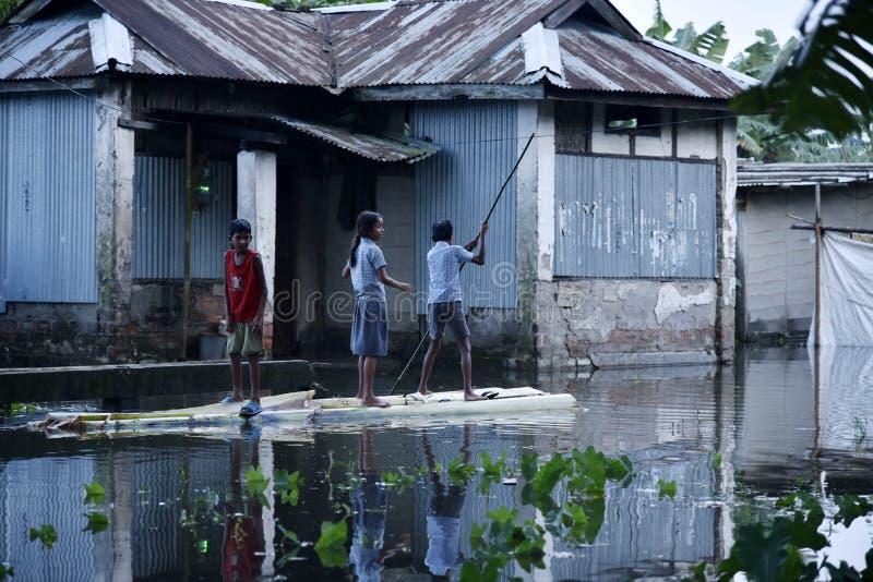 as crianças remam uma jangada perto de uma casa submersa imagens de stock