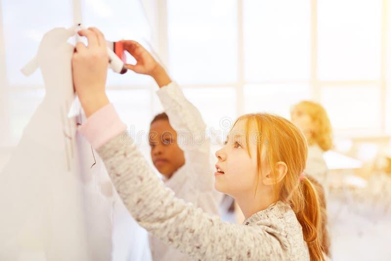 As crianças resolvem a tarefa junto no quadro-negro fotos de stock
