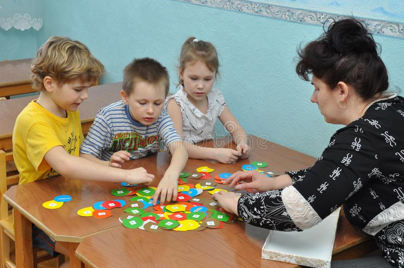 As crianças são contratadas com auxílios de treinamento no jardim de infância imagem de stock