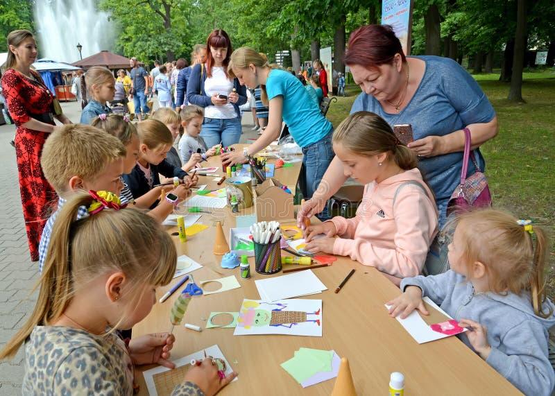 As crianças são contratadas no applique do papel em uma classe mestra no parque fotos de stock royalty free