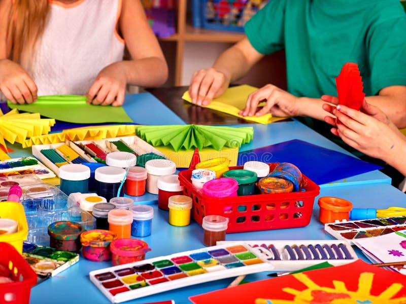 As crianças são contratadas no origâmi e na pintura fotografia de stock