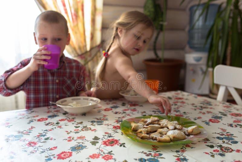 As crianças são irmãos que comem o café da manhã, leite, cookies, estilo de vida foto de stock royalty free