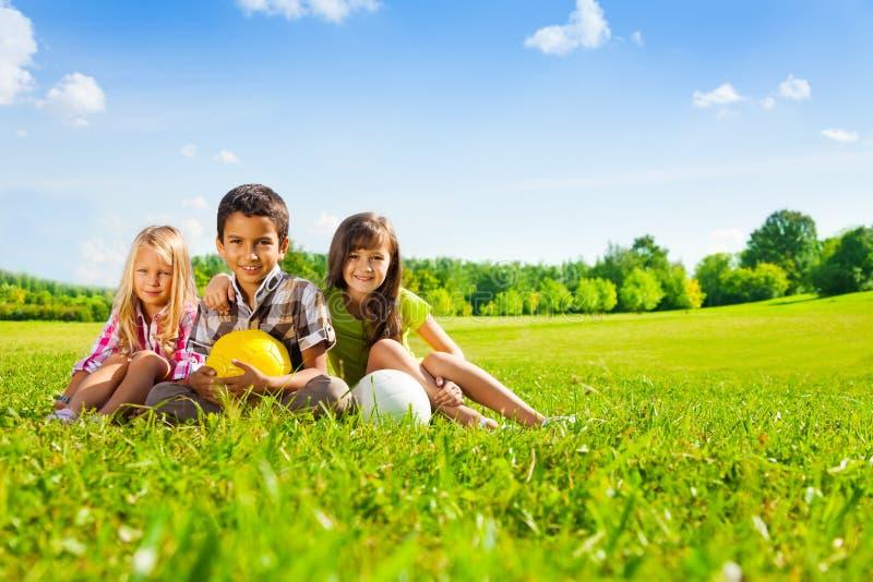 As crianças sentam-se na grama com bolas do esporte fotografia de stock royalty free