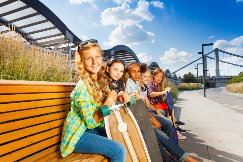 As crianças sentam-se no banco no verão com skates fotografia de stock royalty free