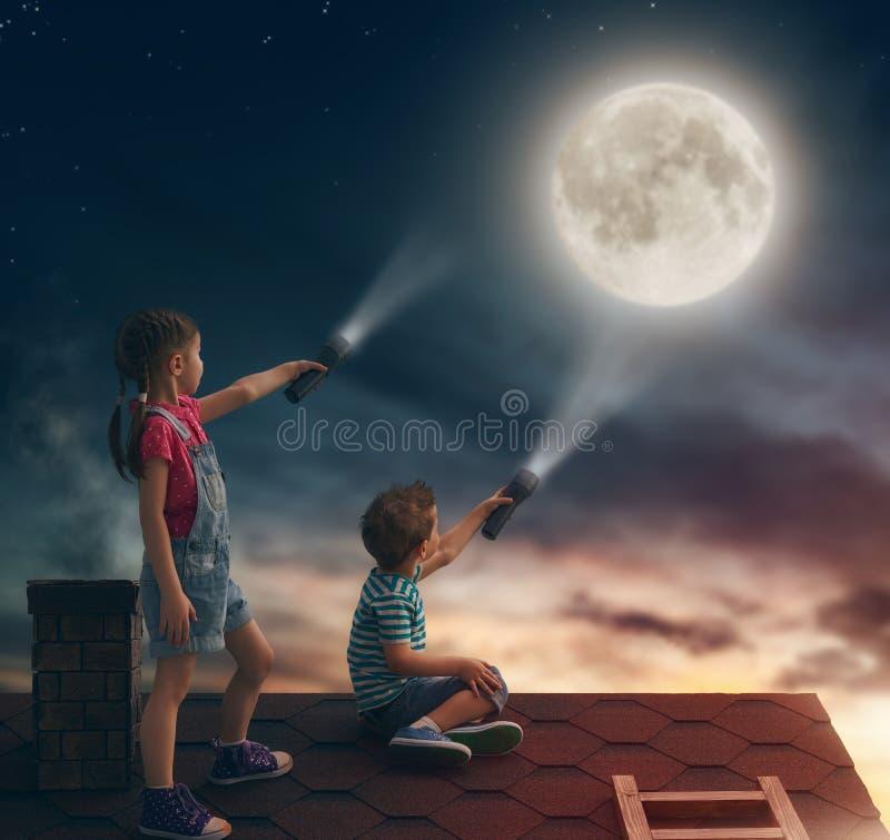 As crianças sentam-se no telhado fotos de stock royalty free