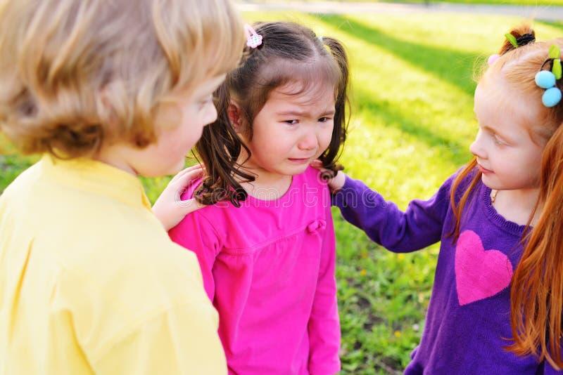As crianças sentem pesarosas para uma menina chorando imagens de stock royalty free