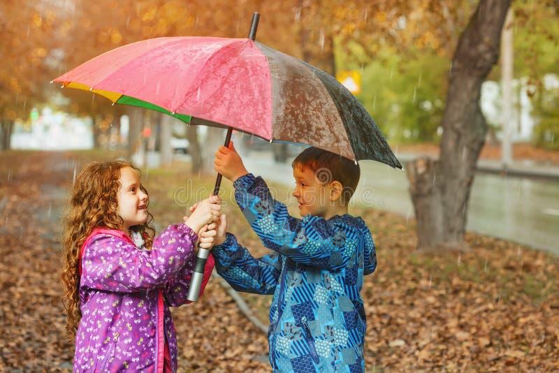 As crianças sob o guarda-chuva apreciam à chuva do outono imagem de stock royalty free
