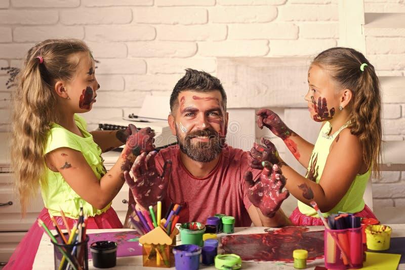 As crianças tiram um paizinho Meninas que tiram na pele da cara do homem com pinturas coloridas imagem de stock royalty free