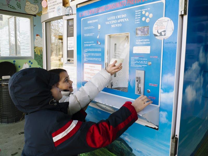 As crianças tomam o leite cru de um distribuidor fotografia de stock