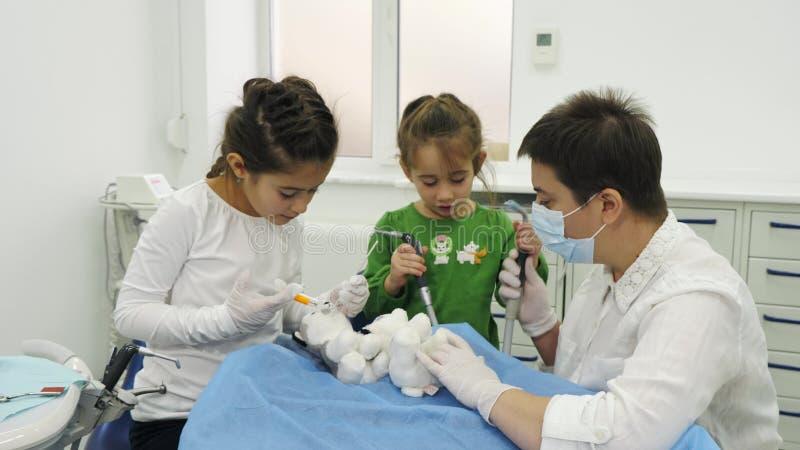 As crianças tratam um brinquedo com o dentista que usa ferramentas dentais diferentes foto de stock
