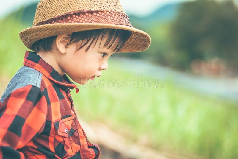 As crianças vestem o chapéu e o assento na terra na exploração agrícola fotografia de stock royalty free