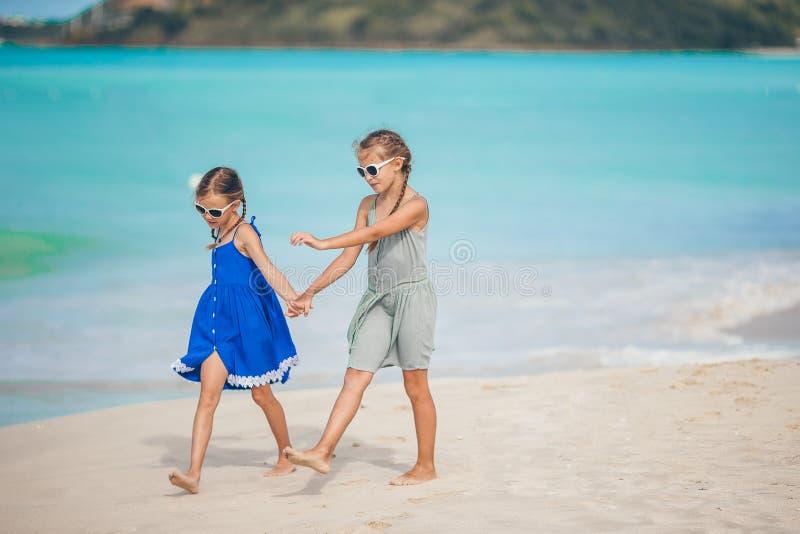 As crian?as felizes pequenas t?m muito divertimento na praia tropical que joga junto fotos de stock royalty free