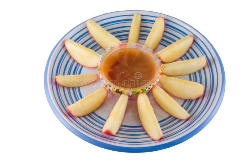 As cunhas de Apple com caramelo mergulham no branco fotos de stock