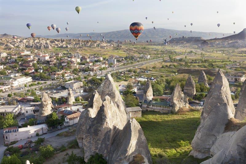 As dúzias dos balões voam sobre os vales em Cappadocia foto de stock royalty free