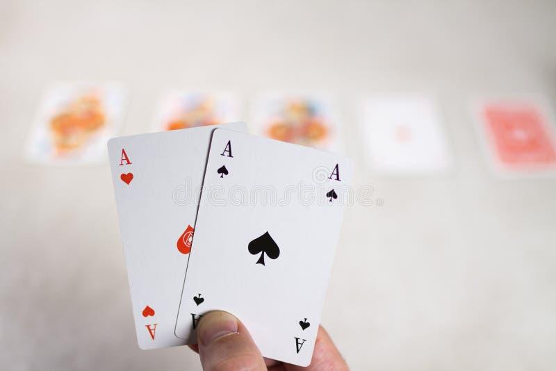 As de la tenencia dos de la mano delante de otras tarjetas foto de archivo