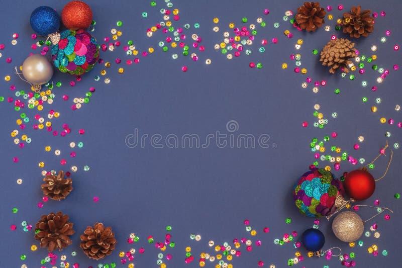 as decorações da Natal-árvore multi-coloriram esferas brilhantes e cones naturais em um escuro - fundo azul com o brilho imagem de stock