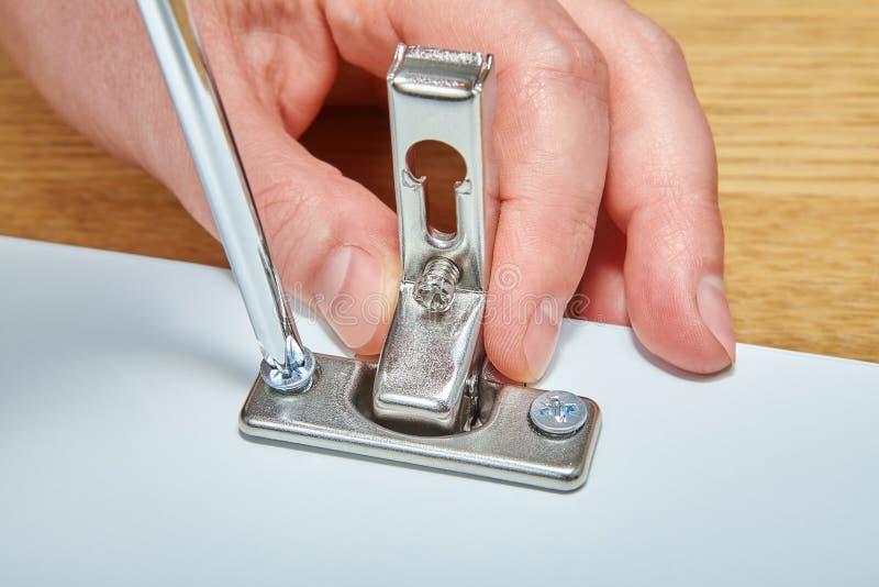 As dobradiças de porta da mobília são apertadas pela chave de fenda imagens de stock royalty free