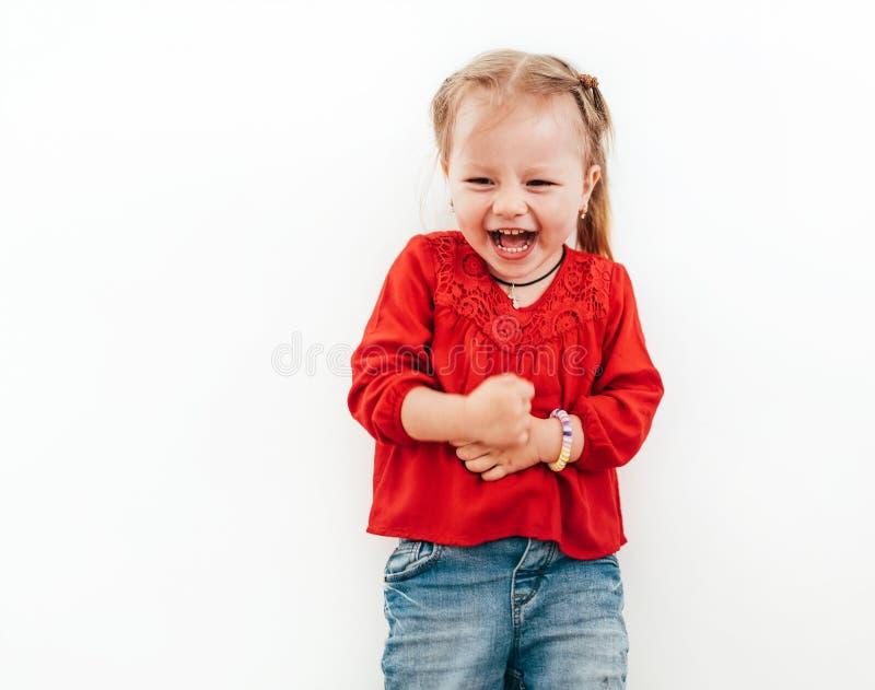 As emoções felizes da menina vestiram a blusa vermelha no fundo branco foto de stock royalty free