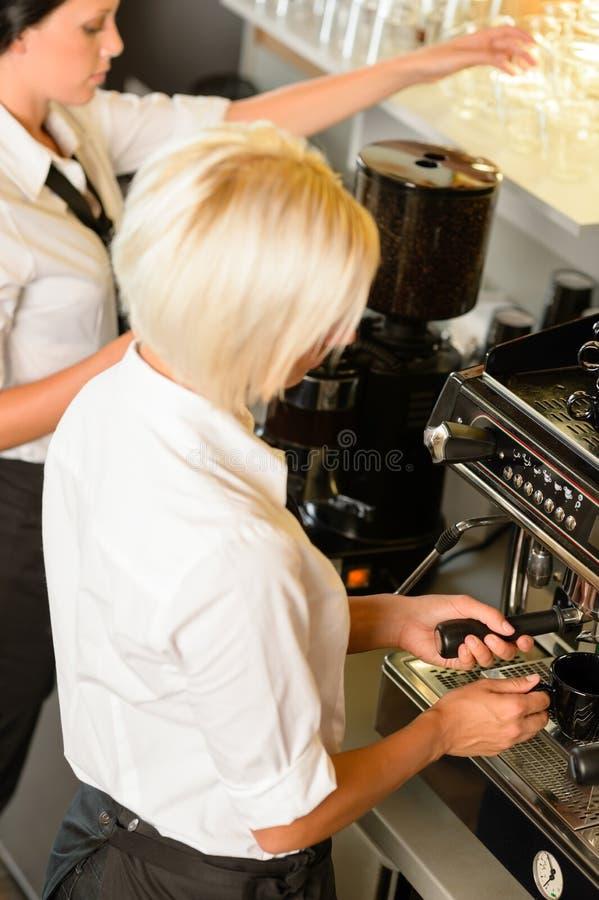 As empregadas de mesa no trabalho fazem o café da máquina do café foto de stock royalty free