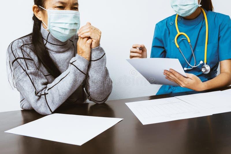 As enfermeiras estão gravando registros pacientes e estão questionando a doença imagens de stock