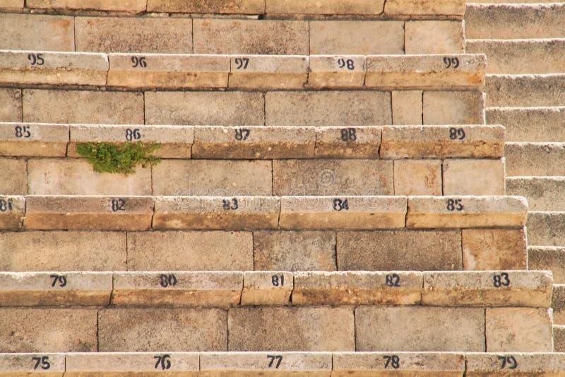 As ervas daninhas crescem sob uma fileira do assento de pedra do teatro em ruínas antigas fotos de stock