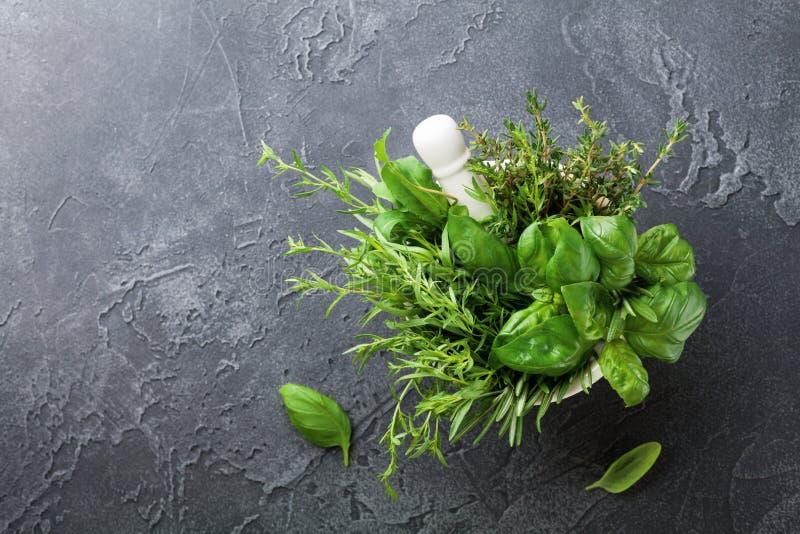 As ervas verdes frescas do jardim no almofariz rolam na opinião de tampo da mesa de pedra preta Tomilho, alecrins, manjericão, e  fotografia de stock royalty free