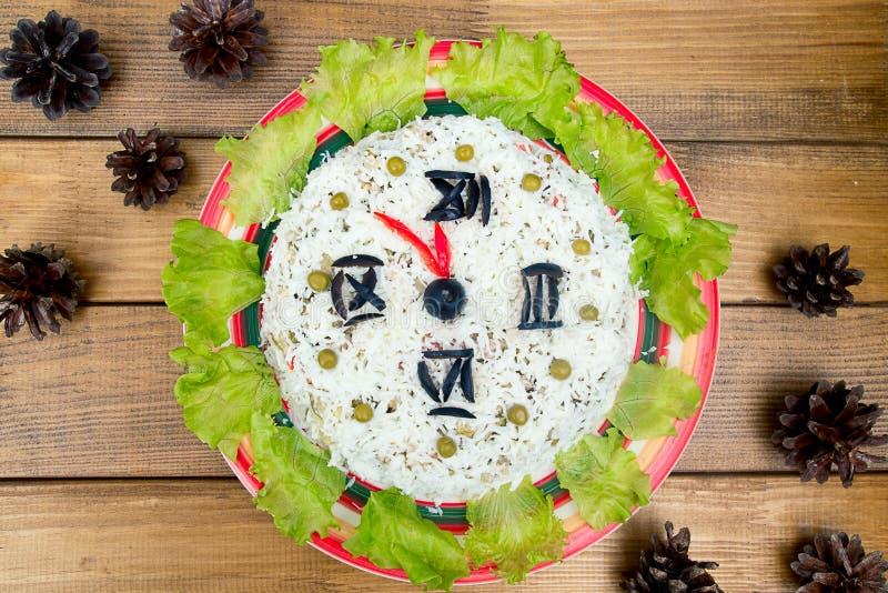 As ervilhas de verdes das azeitonas do arroz da salada do Natal - face do relógio de ano novo do conceito, meia-noite, abeto verm fotos de stock royalty free