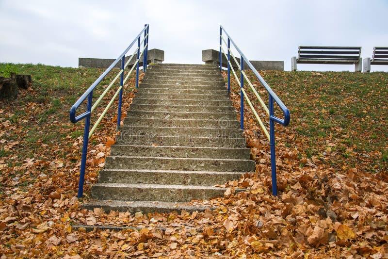 As escadas à caminhada lateral no parque com o céu na queda imagem de stock