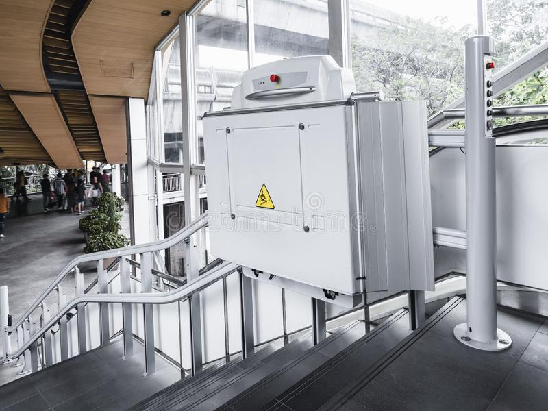 As escadas da inabilidade levantam o elevador da cadeira de rodas da construção pública da facilidade imagem de stock