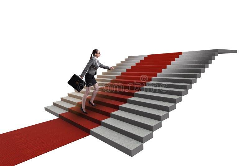 As escadas de escalada da mulher de negócios nova e o tapete vermelho fotografia de stock