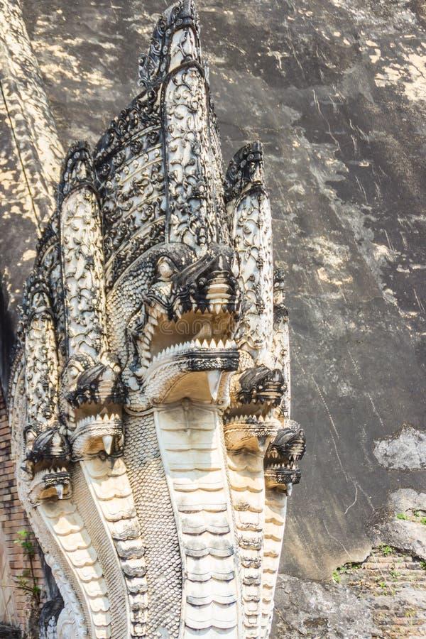 As escadas que conduzem à entrada são guardadas pelos grandes Nagas velhos, serpente mítico como criaturas em Wat Chedi Luang, Ch fotos de stock royalty free