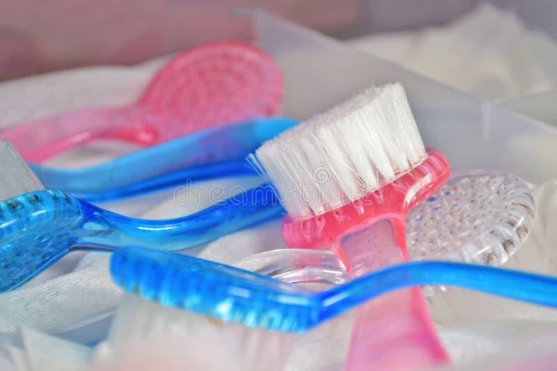 As escovas azuis e cor-de-rosa para o tratamento de mãos e o pedicure do hardware na gaveta da mesa, secam após a esterilização foto de stock