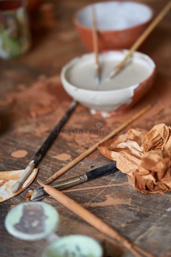 As escovas de pintura mergulham na bacia cerâmica no worktop em uma oficina do oleiro, close-up, foco seletivo fotos de stock royalty free