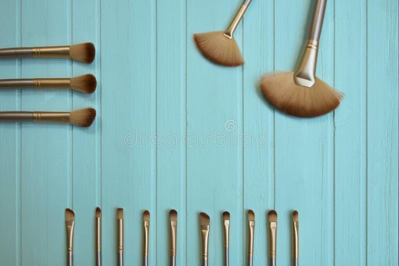 As escovas e as ferramentas profissionais da composição para a mulher, compõem produtos foto de stock