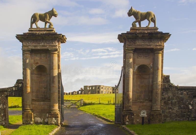 As esculturas do leão sobre a pedra bloqueiam cargos na entrada da porta do ` s do bispo à mangueira de Mussenden em Irlanda do N imagens de stock